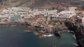 Tiro aéreo Ciudad de vacaciones de la montaña con los muchos hoteles, las palmeras y la otra vegetación Océano azul y las ondas q metrajes