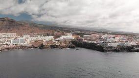 Tiro aéreo Ciudad de vacaciones de la montaña con los muchos hoteles, las palmeras y la otra vegetación Océano azul y las ondas q almacen de metraje de vídeo