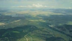 Tiro aéreo da central elétrica de energias solares distante e uma exploração agrícola de vento na Espanha foto de stock royalty free