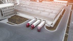 Tiro aéreo da doca de carga industrial do armazém onde muito caminhão fotografia de stock