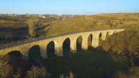 Tiro aéreo da ponte railway de pedra no por do sol com sombra interessante 4k vídeos de arquivo