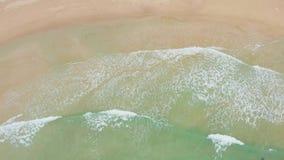 Tiro aéreo das ondas de oceano que deixam de funcionar contra uma praia bonita filme