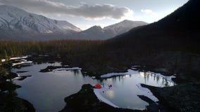 Tiro aéreo de acampar con el caminante rodeado por el lago en montañas almacen de metraje de vídeo