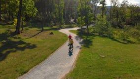 Tiro aéreo de dois rapazes pequenos que montam bicicletas em um parque video estoque
