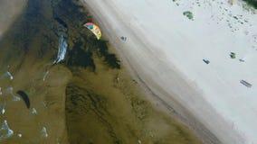 Tiro aéreo de kiteboarders y kitesurfers de la opinión superior 4k del abejón aéreo de Letonia del mar Báltico almacen de metraje de vídeo