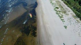 Tiro aéreo de kiteboarders y kitesurfers de la opinión superior 4k del abejón aéreo de Letonia del mar Báltico metrajes