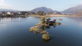 Tiro aéreo de la órbita en la distancia del templo japonés hexagonal construido adentro en el lago fuji almacen de video