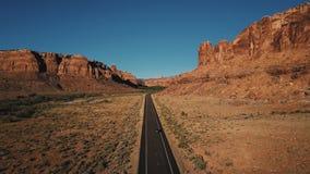 Tiro aéreo de la conducción de automóviles a lo largo del camino americano recto de la carretera del desierto entre canto atmosfé metrajes