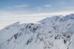 Tiro aéreo de la cordillera nevosa en un día de invierno soleado Imagen de archivo libre de regalías