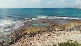 Tiro aéreo de la costa del océano azul y de la playa rocosa con las ondas que salpican contra rocas Opinión del abejón de la cost almacen de video