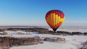 Tiro aéreo de la mosca de la gente en un globo brillante grande sobre el efecto del Carro-enfoque del bosque del invierno almacen de metraje de vídeo