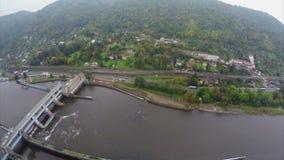 Tiro aéreo de la presa del río, pequeñas montañas del pueblo, tráfico de coche almacen de video