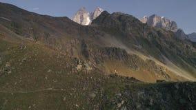 Tiro aéreo de las montañas que suben de un hombre en un día soleado en otoño metrajes