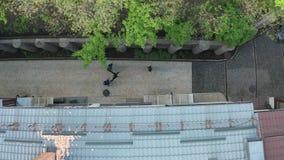 Tiro aéreo de los asaltantes que atacan al hombre en carril de la ciudad almacen de metraje de vídeo