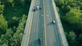 Tiro aéreo de los coches, del corredor y del ciclista moviéndose a lo largo de la carretera por la tarde Imágenes de archivo libres de regalías