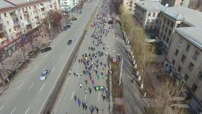 Tiro aéreo de los corredores de maratón de la ciudad que corren en el camino vacío almacen de video