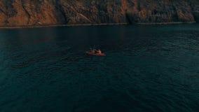 Tiro aéreo de los pares kayaking en el mar durante día de verano