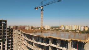 Tiro aéreo de los trabajadores en una construcción, estructura en el proceso a ser estructura metrajes