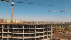 Tiro aéreo de los trabajadores en una construcción, estructura en el proceso a ser estructura almacen de metraje de vídeo