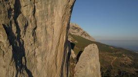 Tiro aéreo de montañas y de rocas que sorprenden en Crimea Shaan-Kaja Vuelo cerca del acantilado enorme usado para el salto de la almacen de video
