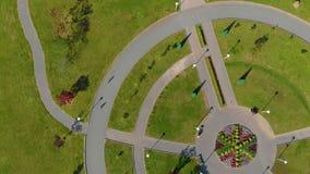 Tiro aéreo de Topview de dois rapazes pequenos que montam bicicletas em um parque filme