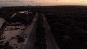 Tiro aéreo de um bulevar perto de Cancun, México no por do sol que filtra acima para a cidade vídeos de arquivo
