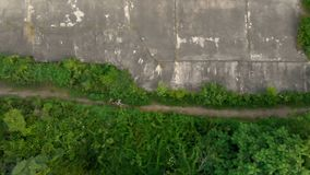 Tiro aéreo de um homem novo e de seu filho que correm no território de uma primeira fortaleza velha da guerra mundial durante o p filme