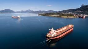 Tiro aéreo de um navio de carga no mar aberto com outros navio e montanhas no fundo fotos de stock royalty free