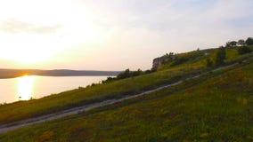 Tiro aéreo de um por do sol perto das rochas As cores vívidas são refletidas na água filme