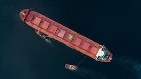 Tiro aéreo de um porto de aproximação do navio de carga com ajuda do navio do reboque imagem de stock royalty free