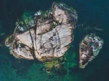 Tiro aéreo de uma ilha rochosa em um oceano imagem de stock royalty free