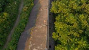 Tiro aéreo de uma jovem mulher que corre sobre uma primeira fortaleza velha da guerra mundial durante o por do sol, nascer do sol video estoque