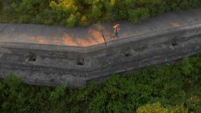 Tiro aéreo de uma jovem mulher que corre sobre uma primeira fortaleza velha da guerra mundial durante o por do sol, nascer do sol filme