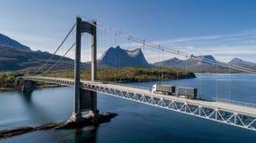 Tiro aéreo de uma ponte sobre Efjord com um caminhão e uma montanha Stortinden no fundo imagens de stock