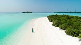 Tiro aéreo de uma posição dos pares em um Sandy Beach limpo pelo mar com água azul claro foto de stock royalty free