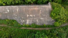 Tiro aéreo de un hombre joven que corre en el territorio de una 1ra fortaleza vieja de la guerra mundial durante la puesta del so almacen de video