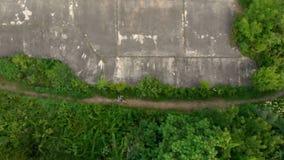 Tiro aéreo de un hombre joven que corre en el territorio de una 1ra fortaleza vieja de la guerra mundial durante la puesta del so metrajes