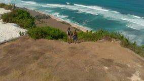 Tiro aéreo de una familia feliz que visita una playa remota - nyang- del nyang en la isla de Bali Colocación en una roca que mira metrajes