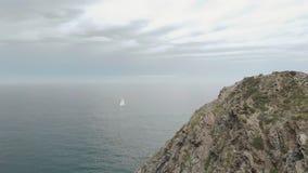 Tiro aéreo de una navegación sola del yate en el mar, con la roca enorme en el primero plano metrajes
