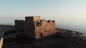 Tiro aéreo del abejón del castillo viejo en los paphos Chipre durante puesta del sol con el mar en fondo almacen de video