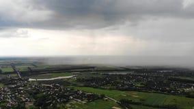 Tiro aéreo del abejón de la precipitación pesada que se acerca al pueblo suburbano almacen de metraje de vídeo