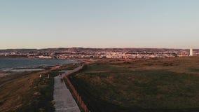 Tiro aéreo del abejón de la trayectoria peatonal a lo largo del mar Mediterráneo con el faro en Paphos Chipre almacen de metraje de vídeo