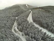 Tiro aéreo del camino nevado en las montañas cárpatas del campo Foto de archivo
