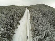Tiro aéreo del camino nevado en las montañas cárpatas del campo con el coche en manera Foto de archivo