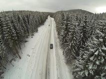 Tiro aéreo del camino nevado en las montañas cárpatas del campo con el coche en manera Fotografía de archivo