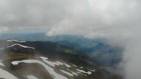 Tiro aéreo del canto cárpato cubierto con nieve, las nubes y la niebla almacen de video