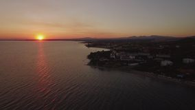 Tiro aéreo del centro turístico griego en costa de mar, visión en la puesta del sol almacen de metraje de vídeo