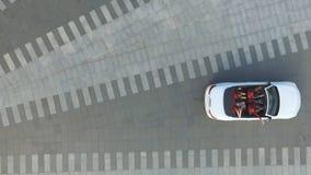 Tiro aéreo del coche convertible blanco con cuatro mujeres irreconocibles jovenes que comienzan paseo en el cuadrado de ciudad mu metrajes
