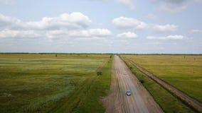 Tiro aéreo del coche en el camino rural