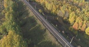 Tiro aéreo del ferrocarril entre los árboles del otoño en bosque en octubre Foto de archivo